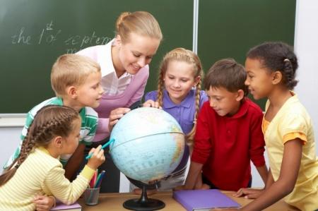 gyerekek a tanárnőkükkel és egy földgömbbel