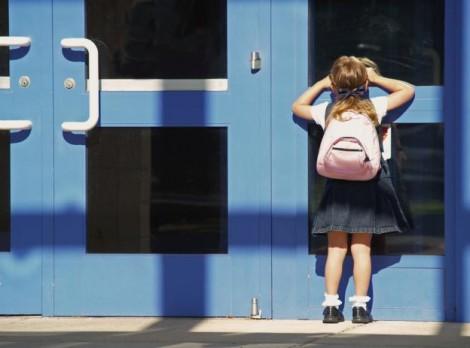 kislány bekukucskál egy kék ajtón