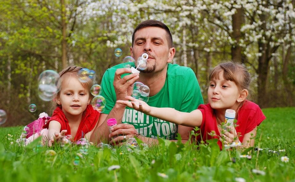 lányok buborékot fújnak az apukájukkal