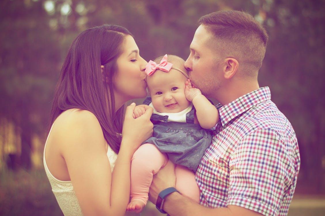 szülők puszilják a kislányukat