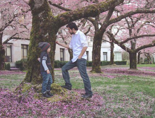 felnőttel beszélgető kislány, fák alatt