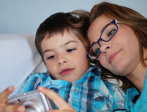 kisfiú telefont néz az anyukájával