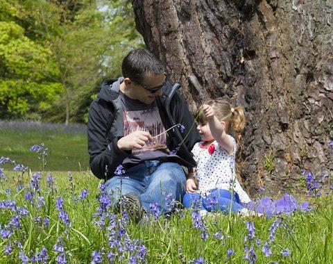 kislány ül a fűben az apukájával