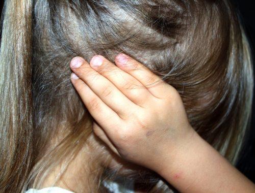 fülét befogó kislány