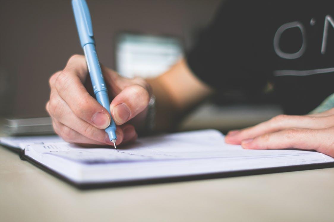 fiú kék tollal ír a füzetébe