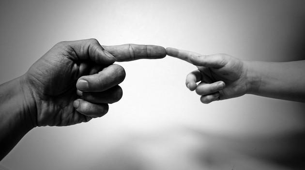 apuka és gyereke összeérintik az ujjukat