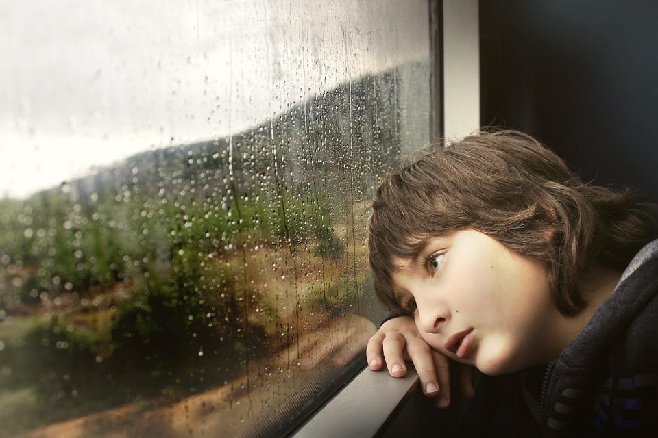 szomorú kisfiú kinéz az ablakon