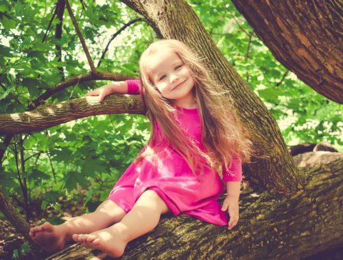 kislány rózsaszín ruhában a fán
