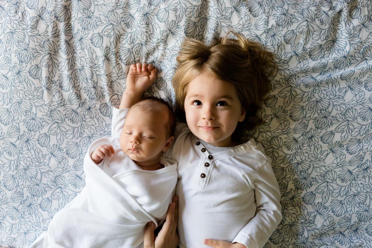 kislány fekszik az ágyon a kistestvérével