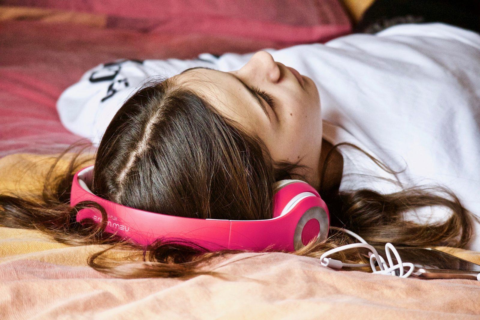 tinilány fekszik az ágyon fülhallgatóval a fején