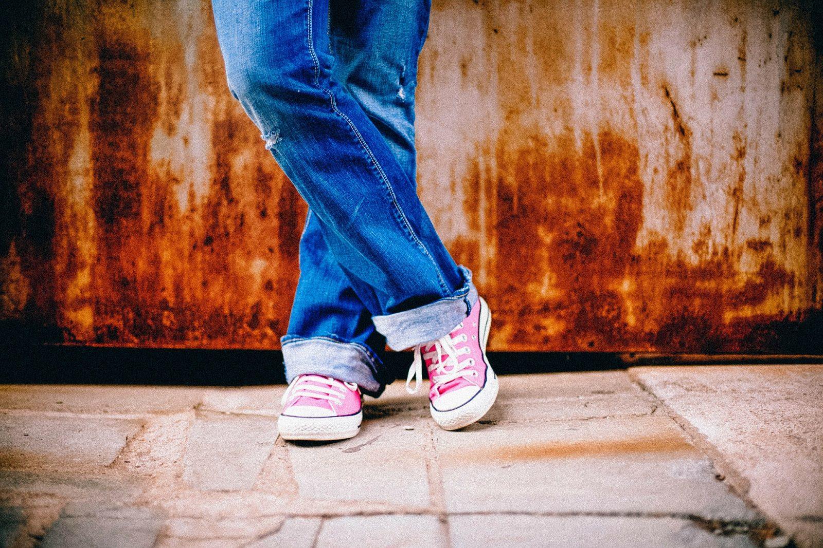 kislány keresztbe tett lábbal, rózsaszín tornacipővel