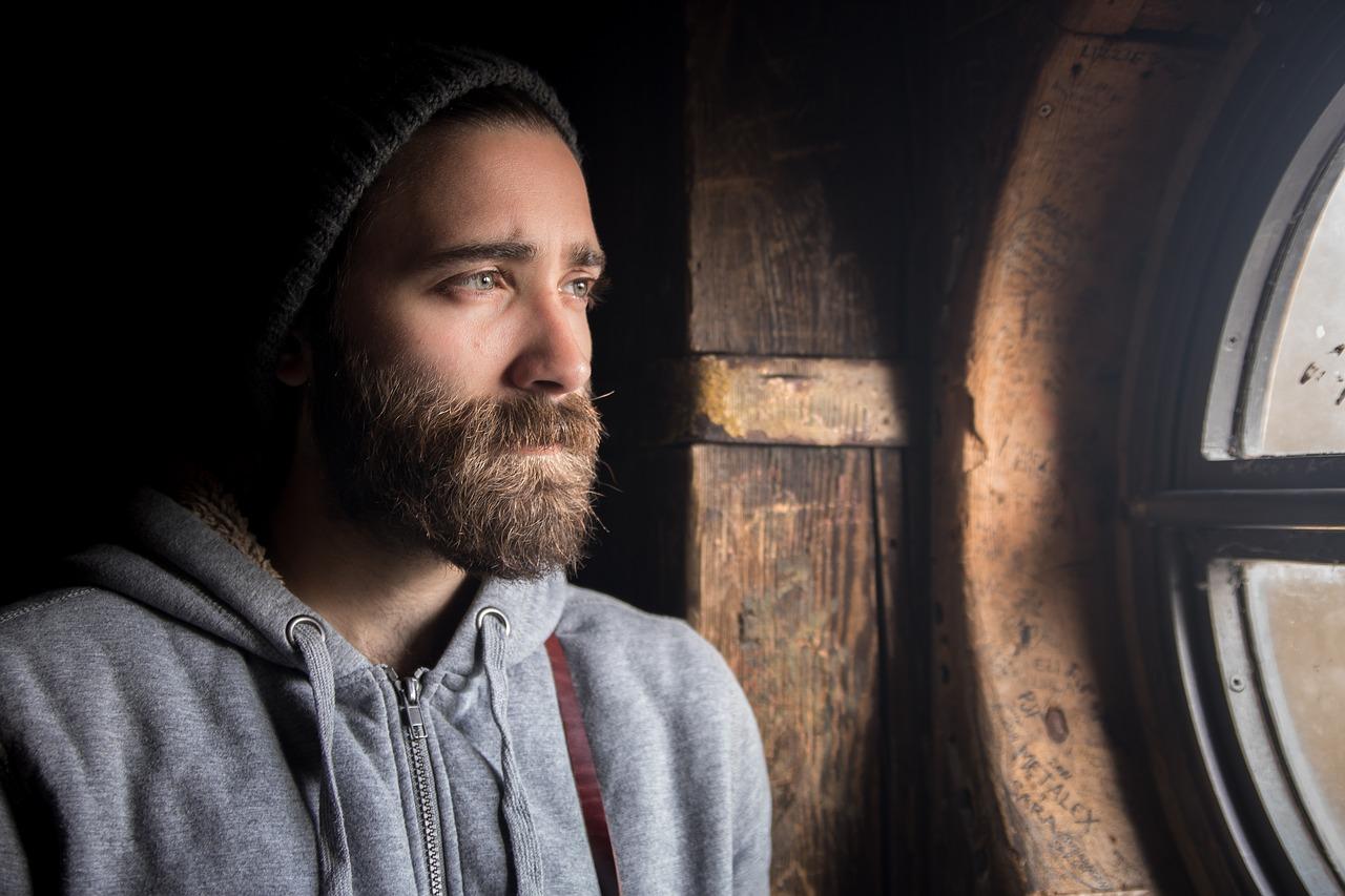 szakállas férfi néz ki egy ablakon