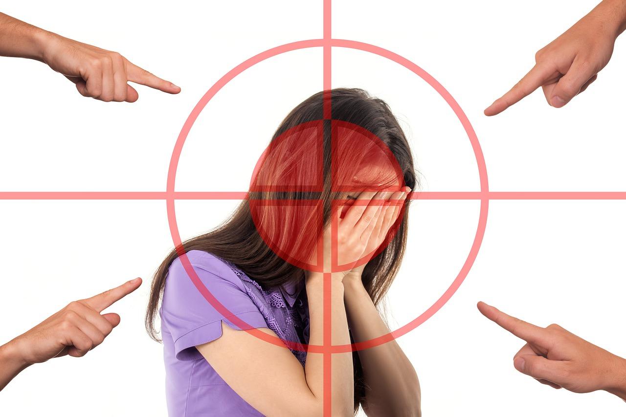 lány eltakarja az arcát, mert ujjal mutogatnak rá