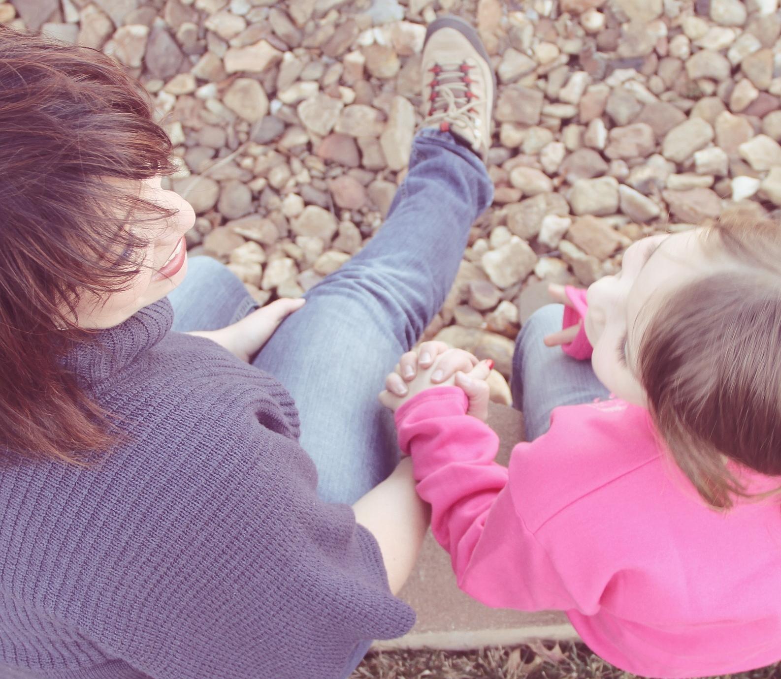 kislány beszélget az anyukájával a kavicsos parton