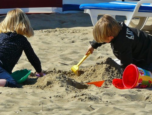 két gyerek játszik a tengerparti homokban