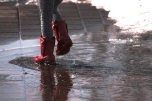kislány sétál a pocsolyában piros csizmával