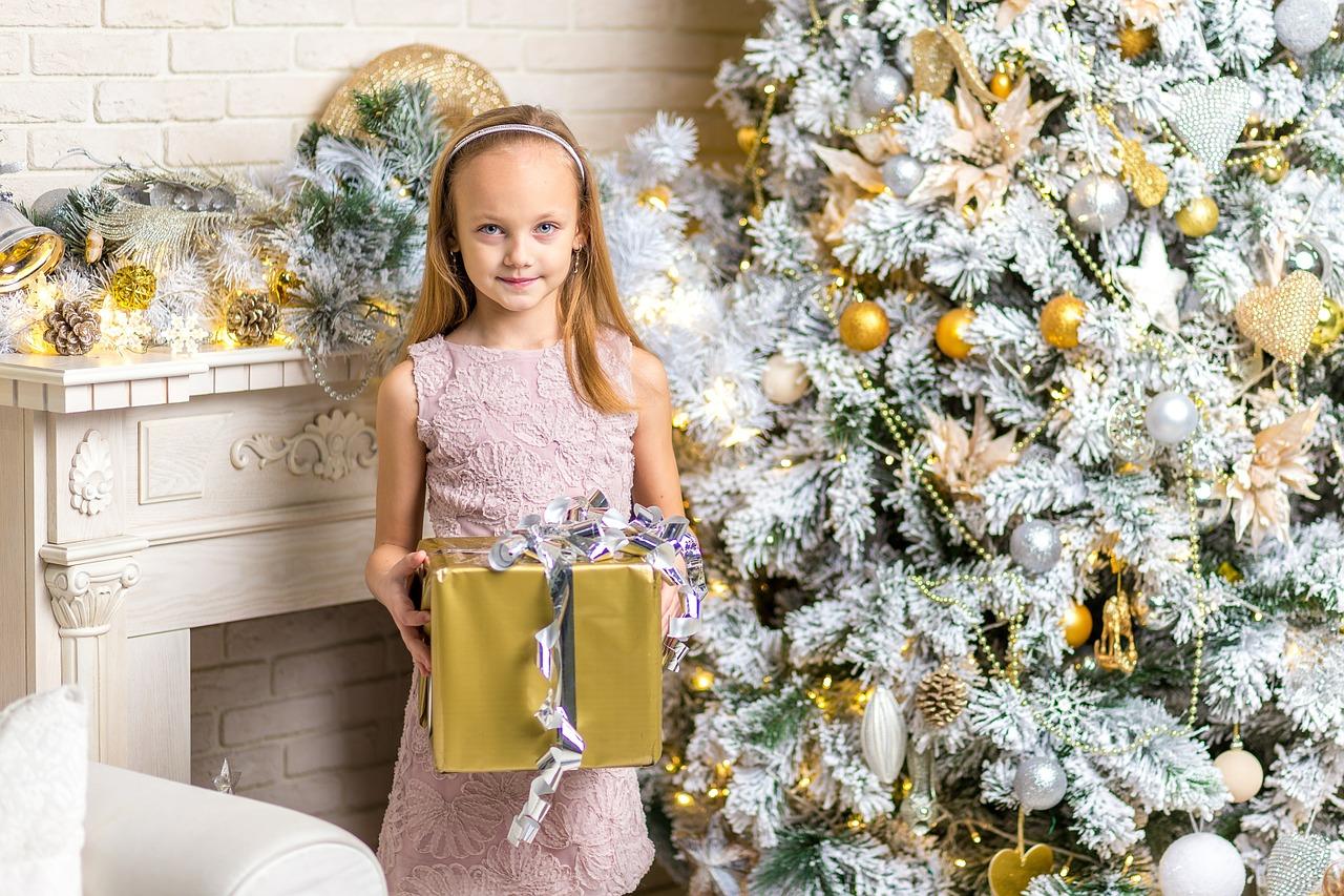 ajándék dobozt tartó kislány a karácsonyfa melett