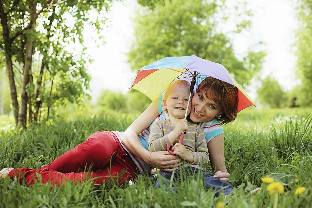 kisfiú és anyukája fekszenek a fűben egy esernyővel