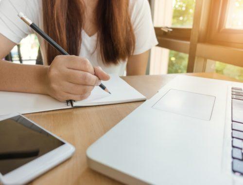 írás füzet laptoppal és telefonnal