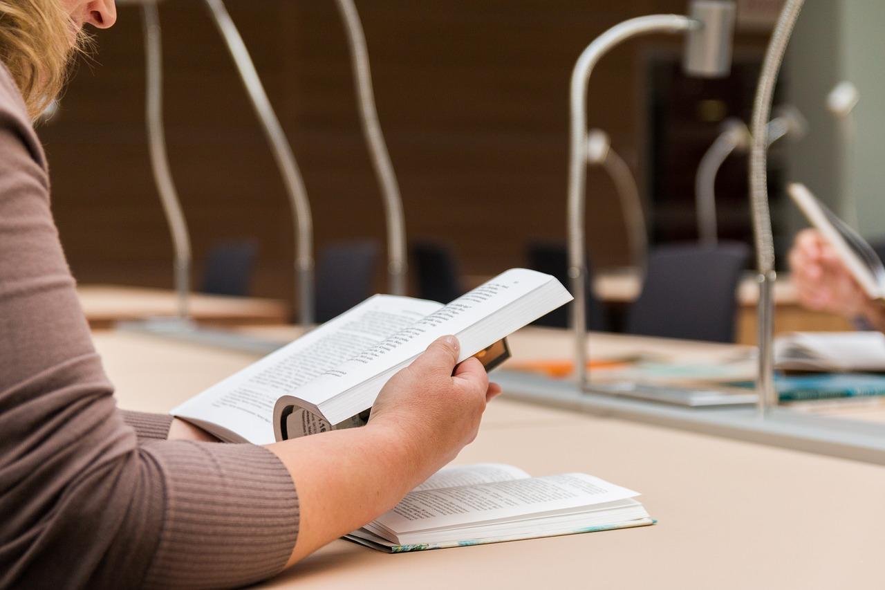 nő egy könyvvel és lámpákkal