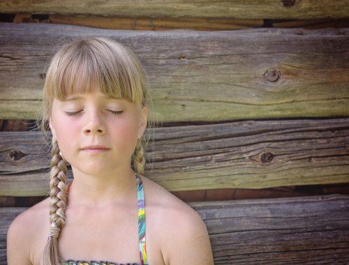 szőke hajú kislány csukott szemmel
