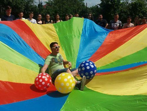 gyerekek kooperációs ernyővel, három pettyes labdával