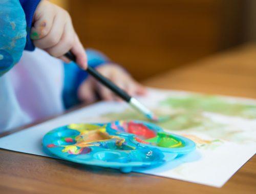 kisgyerek festékkel fest egy paírra