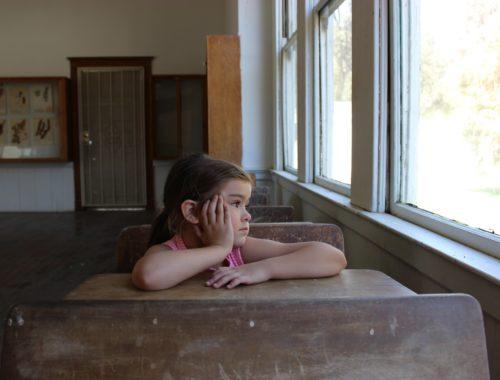 kislány ül az iskolapadban