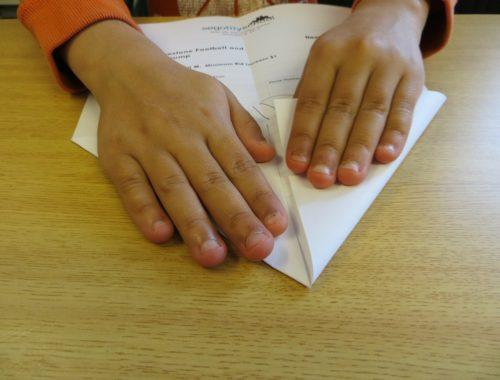 gyerek papírrepülőt hajtogat