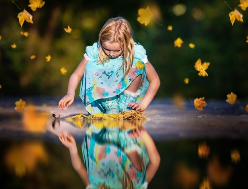 kislány sárga levelekkel játszik a pocsolyában