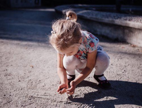 egy kislány guggol és homok van a kezében