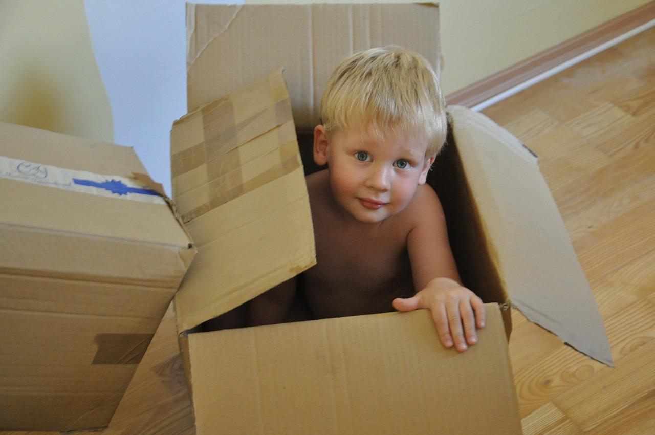 kisfiú egy dobozban ül