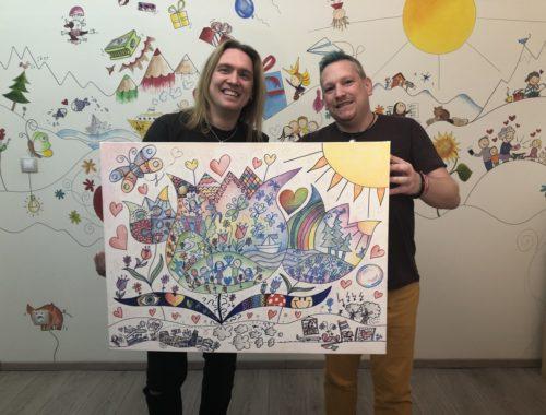 két férfi színes rajzot tart a kezében