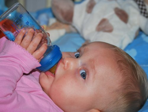 kisbaba cumisüveggel a kezében