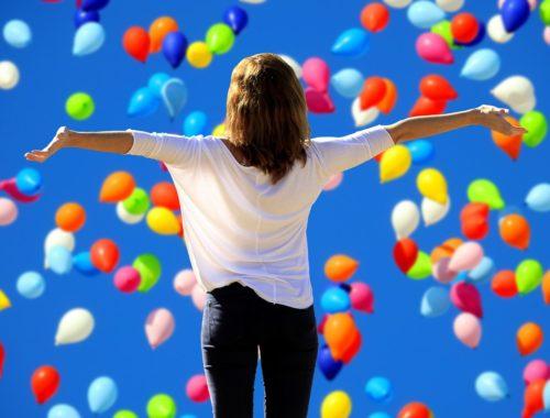 repülő színes légballonok, tárt kezekkel álló nő