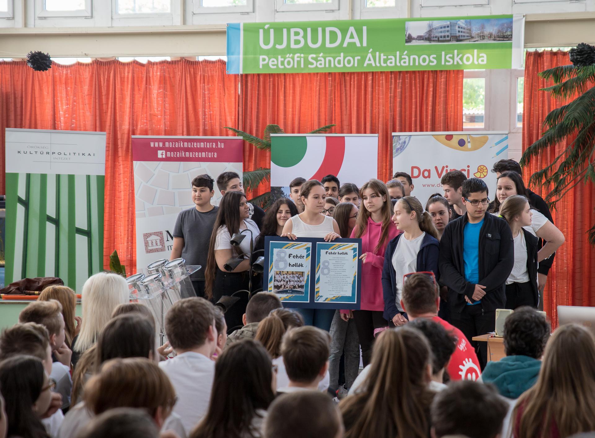 kisiskolások csoportban állnak, előadást tartanak