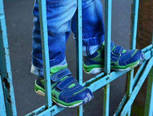 kisfiú kerítésen áll