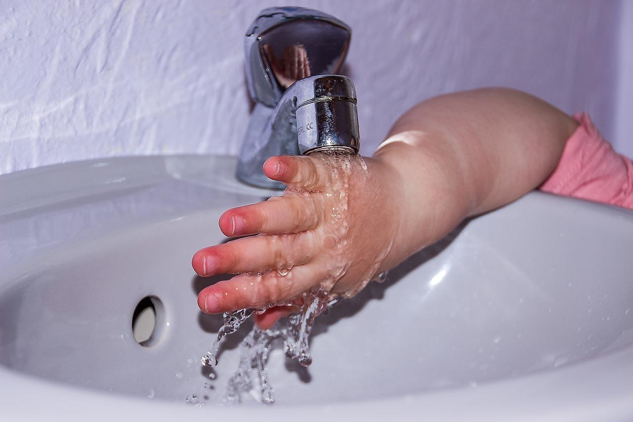 egy kisgyerek víz alá tartja a kezét