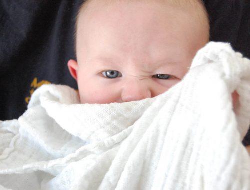 kisbaba grimaszol és elbújik a takarója mögé