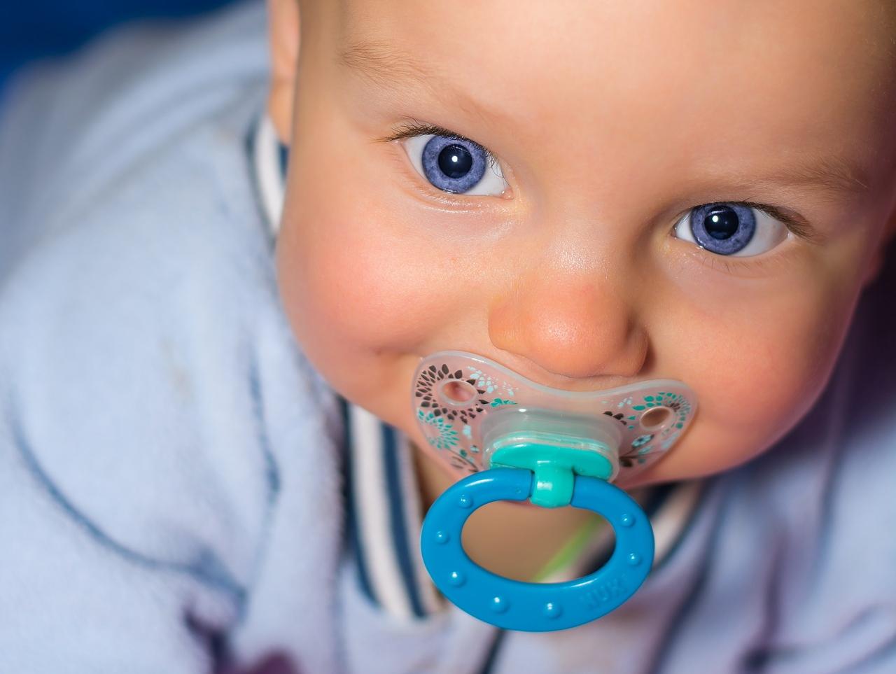 kék szemű kisbaba cumival a szájában