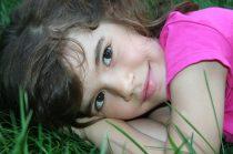 kislány mosolyog a fűben