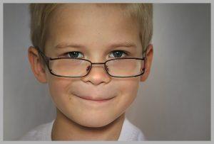 szemüveges kisfiú mosolyog