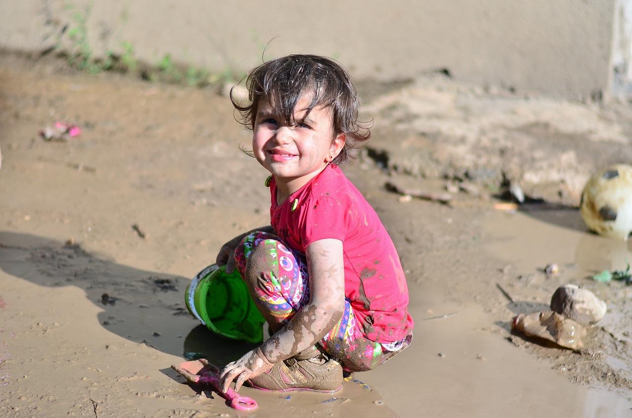 kislány játszik a kavicsos vízparton