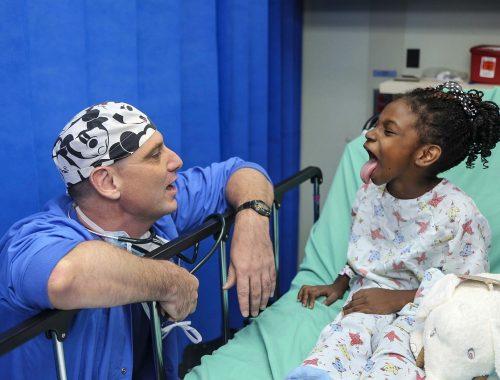 orvos vizsgálja a beteg kislányt, aki kinyújtja a nyelvét
