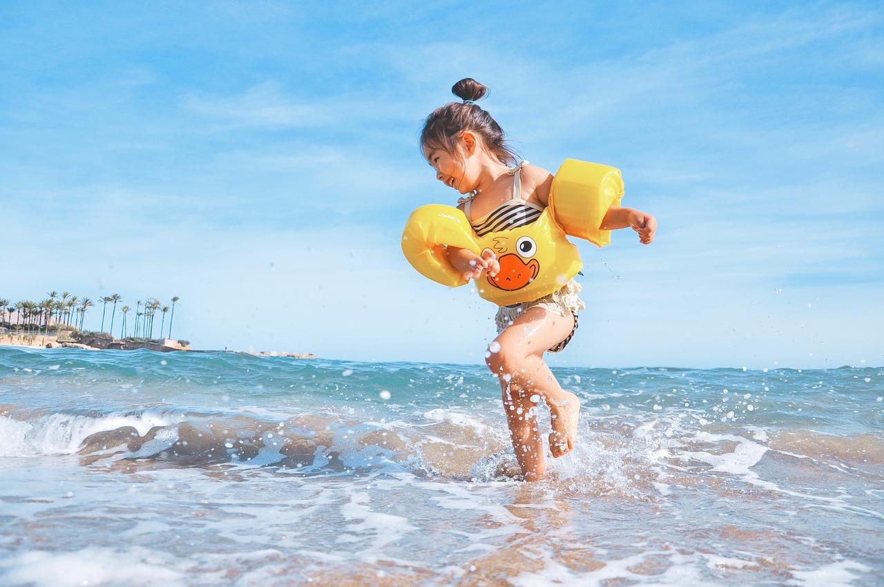 kislány játszik a vízparton fürdőruhában, karúszóval a karján