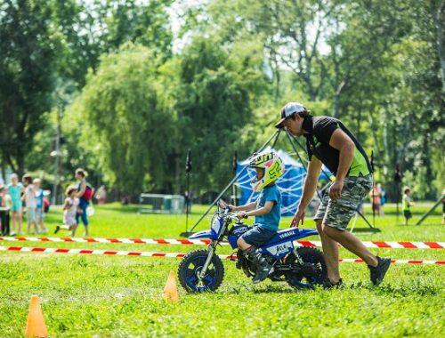 kisfiú motorral megy egy akadálypályán egy férfi segít neki