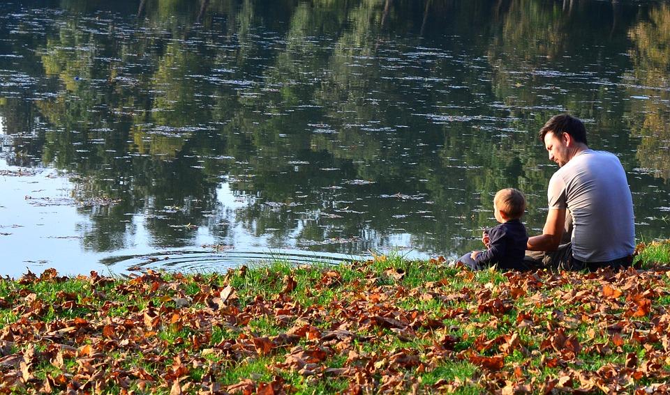 kisfiú ül a tó partján az apukájával