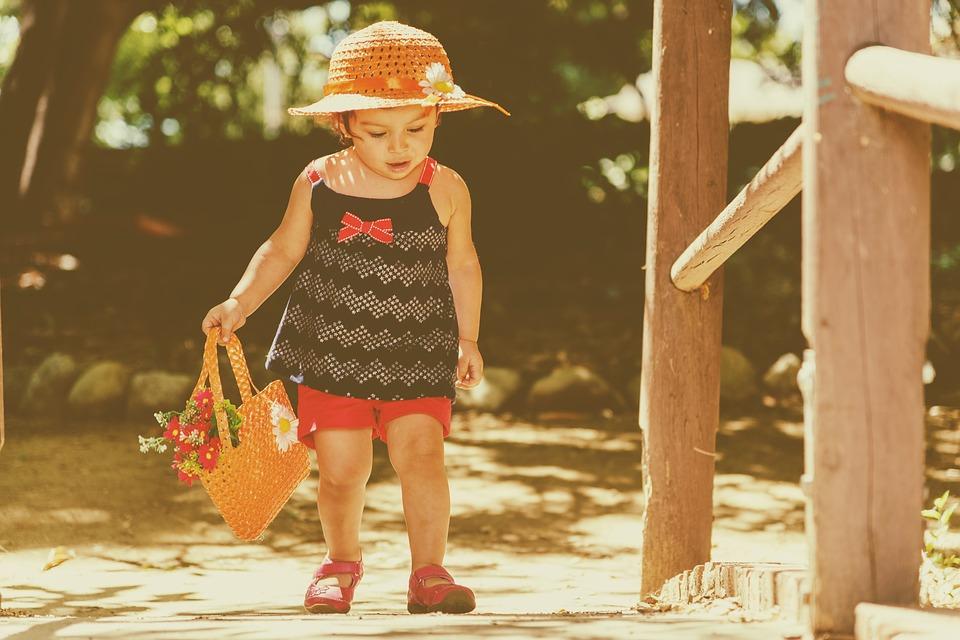 kislány kosár virággal a kezében, kalapban