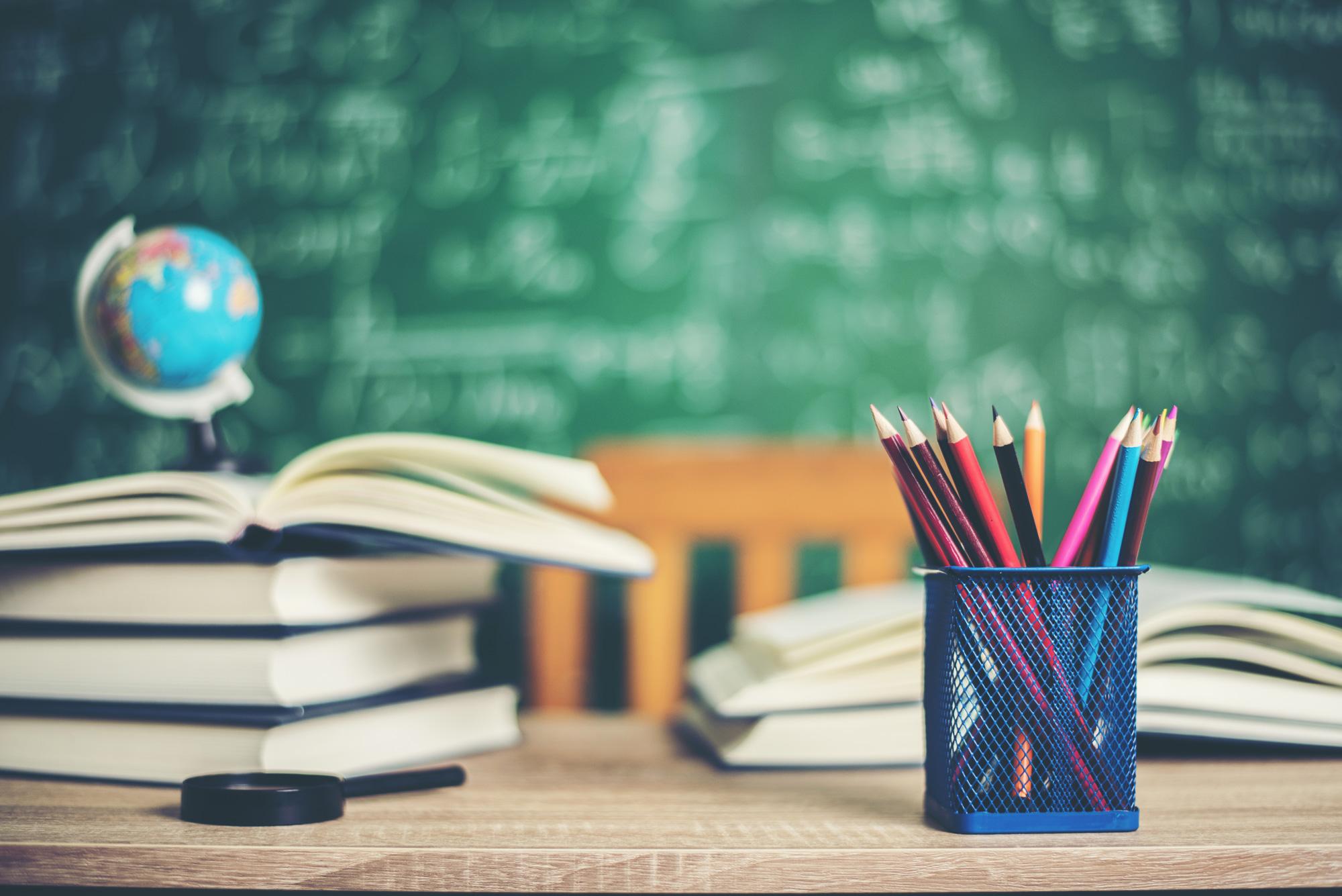 asztalon lévő könyvek, ceruzák és egy Föld gömb