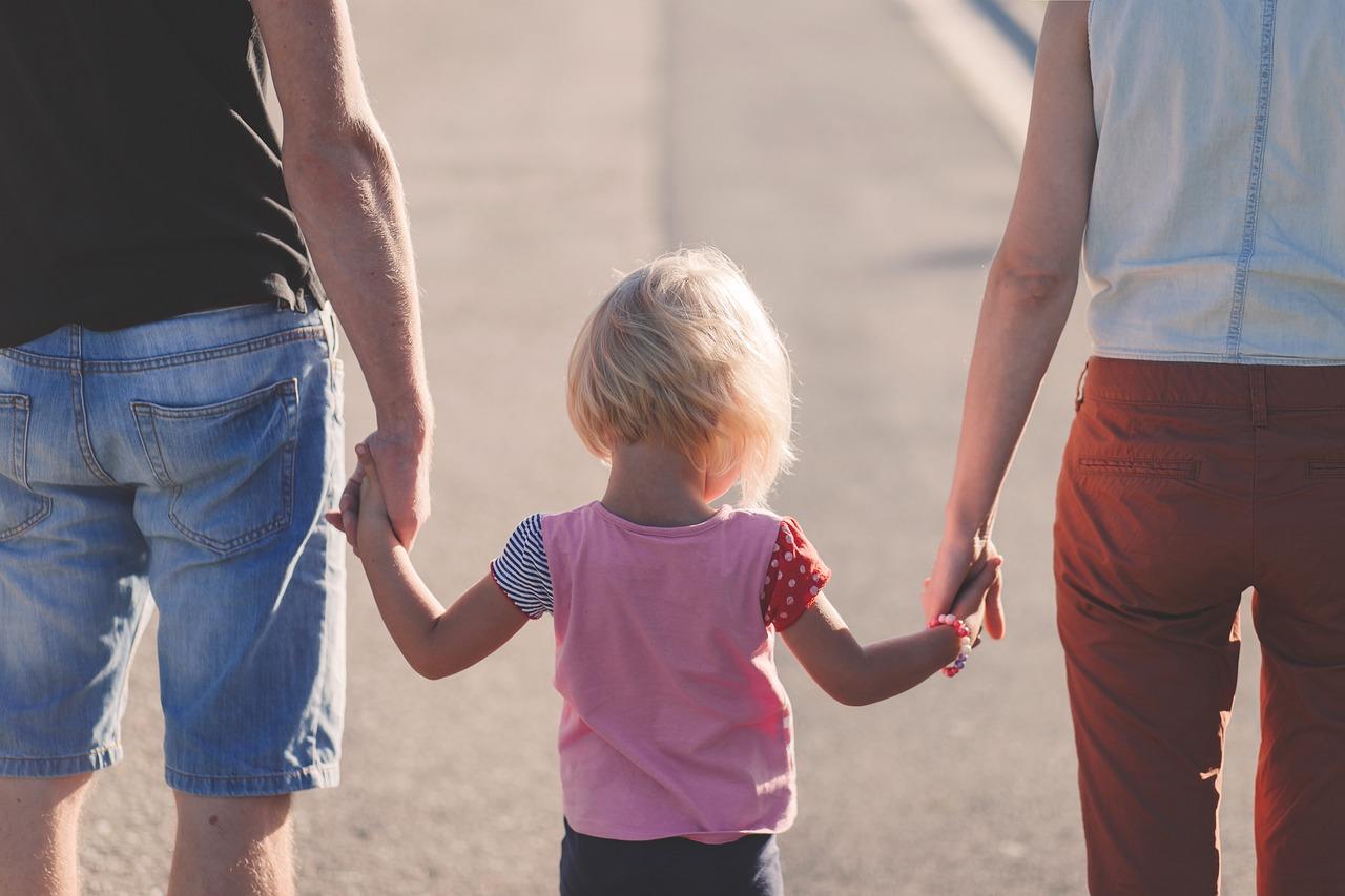 család háttal áll, szülők a gyermekük kezét fogják